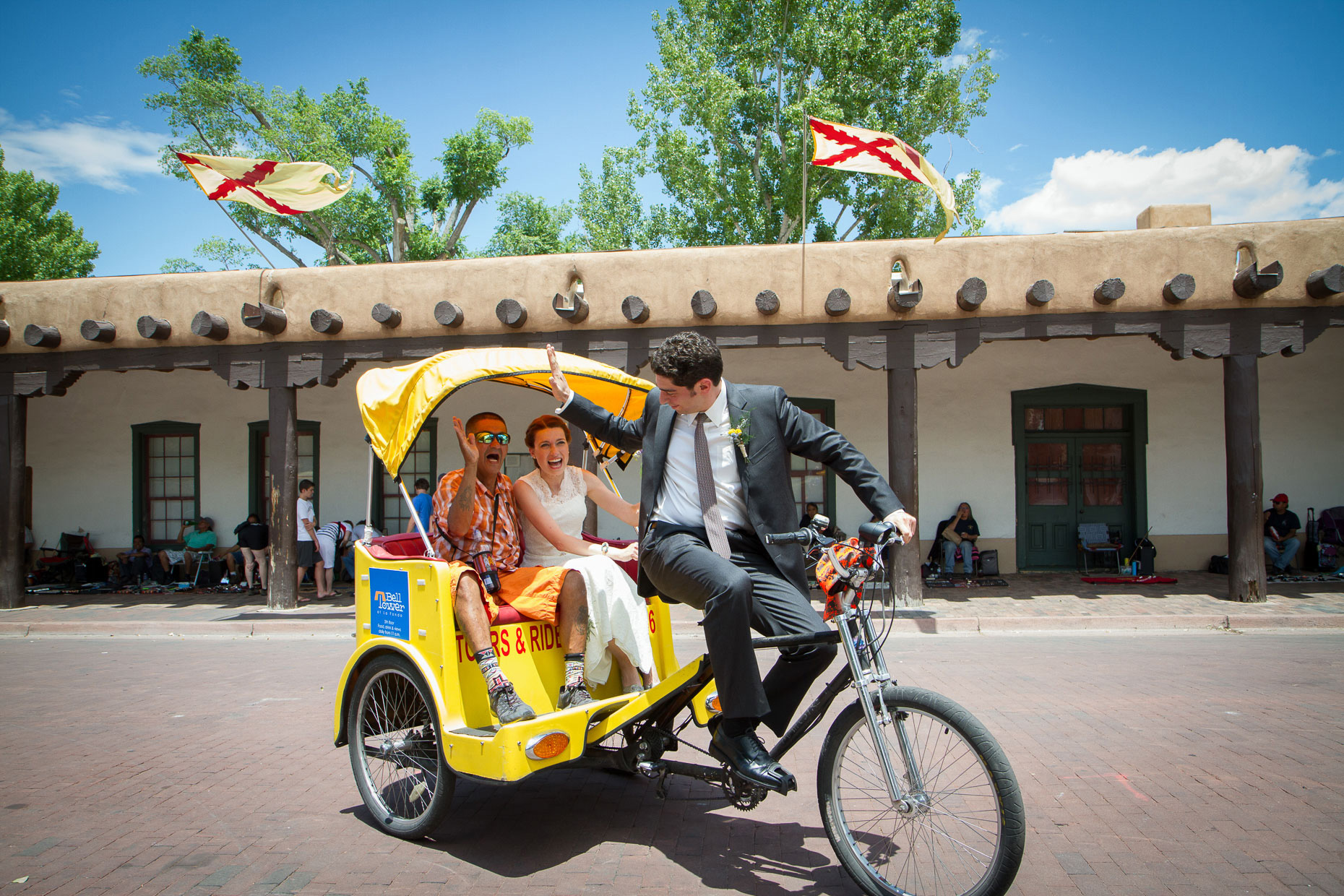 newlywed couple in santa fe pedicabs driving down plaza