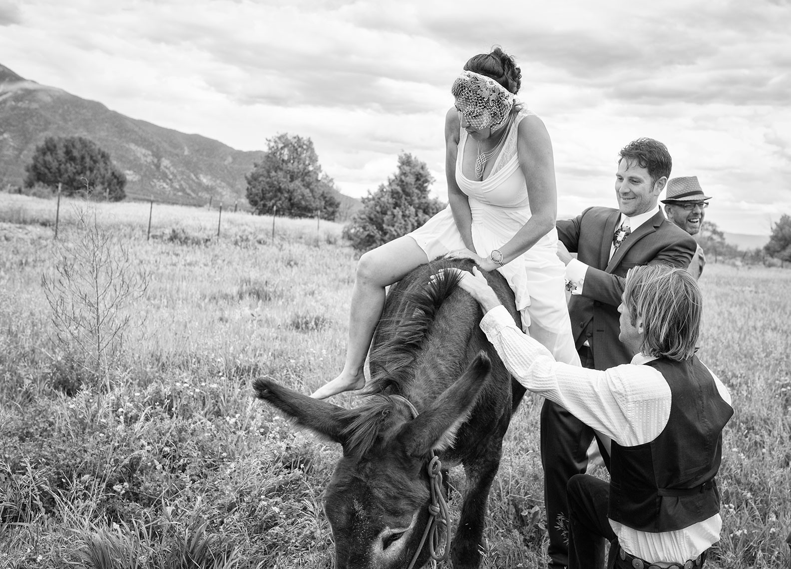 Taos bride gets on donkey with the help of the groom.