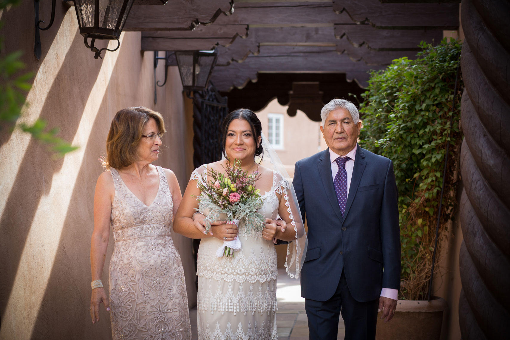La Fonda Wedding Ceremony, bride walks down aisle with mother and blind father