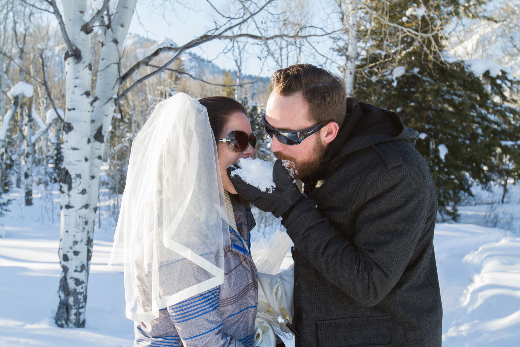 Grand Teton winter wedding, couple eating snow instead of cake