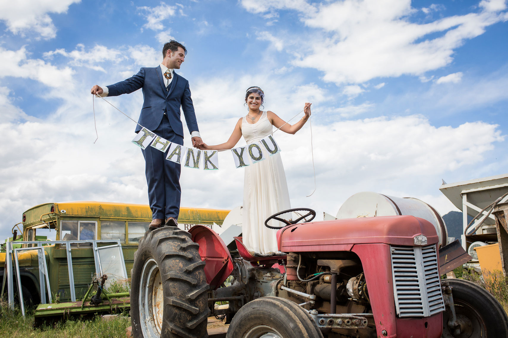 Rustic Taos Wedding, couple holds Thank You signs standing on tractor